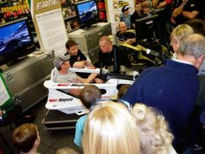 The irony of the occassion was not lost on the watching audience as World Cahampion Indy 500 2008 recieves last minute briefing from racing in the seat simulator around the virtual Indy 500 track.