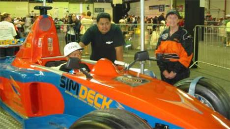 Under the watchful eye of Dad and SimDeck staff, this young chap tries his skill at driving on the Pukekohe race circuit.
